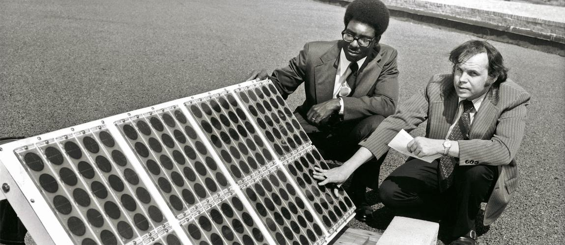 Researchers kneeling next to a solar panel