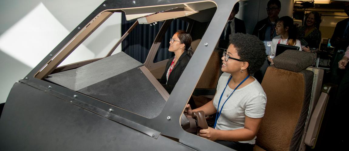 Virginia Tech students sitting in cockpit simulator