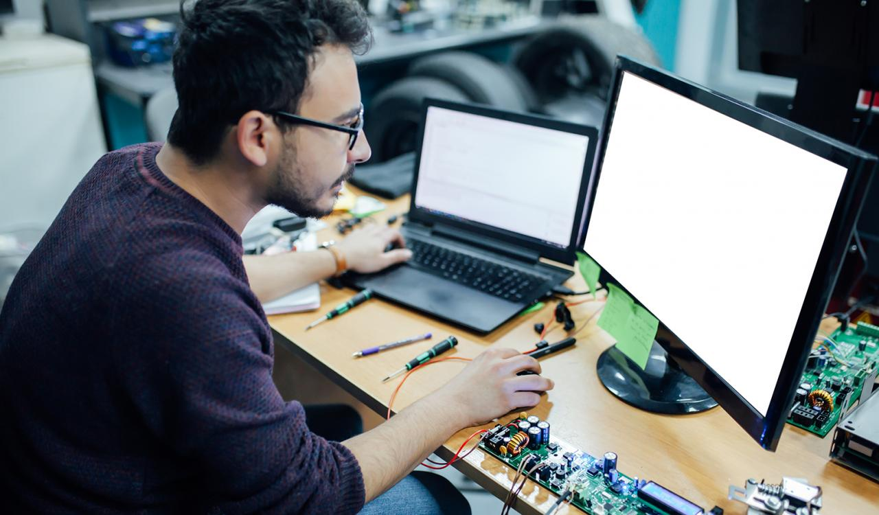 Intern working at a desk with a circuit board in front of him